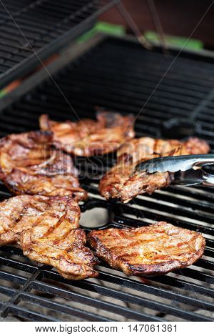 Grilled pork almost ready on the grill with metal tongs