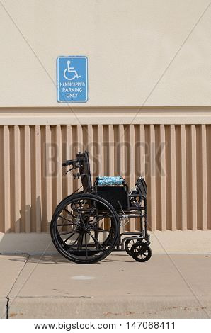 Wheelchair in front of Handicapped Parking Only Sign in parking lots