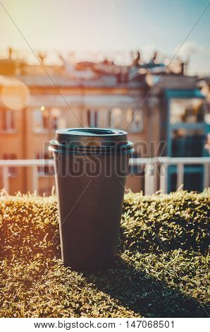 Fresh kraft cup of black coffee or tea on a green grass blurred city roofs background. Coffee break concept. Take away breakfast in the sunny morning outdoor. Enjoy lifestyle modern life concept.