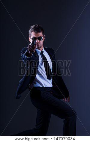 Brave cool man holding a gun on dark background