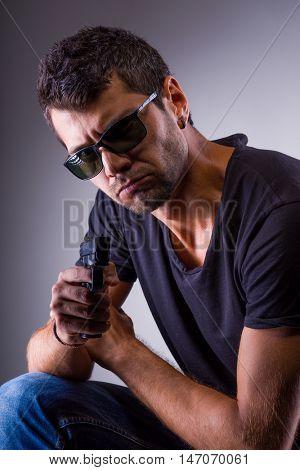 Man holding a handgun over gray background