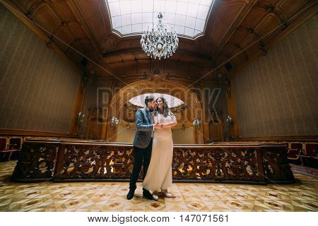 Charming newlywed pair embracing with the background of royal wooden vintage interior.