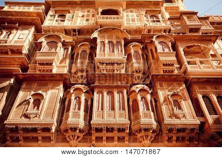 Tall building with carved volumetric shape balconies in area of ancient indian city Jodhpur, India