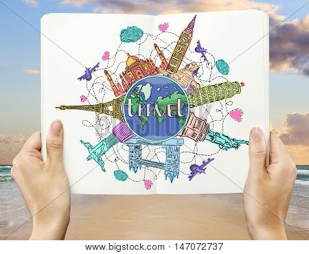 Woman's hands holding open copybook with creative colorful travel doodle on seaside background. Traveling concept