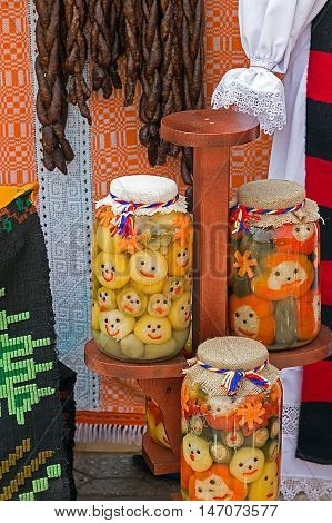 Romanian traditional sausages hanging on a fence and happy pickles