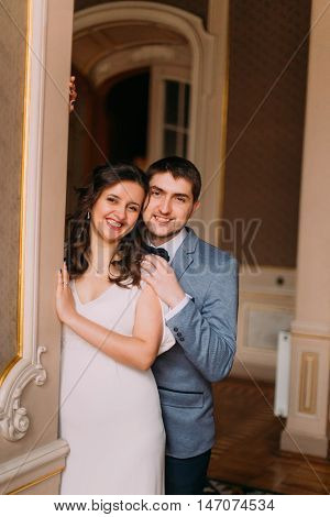 Portrait of beautiful newlywed pair embracinging in vintage victorian mansion interior.