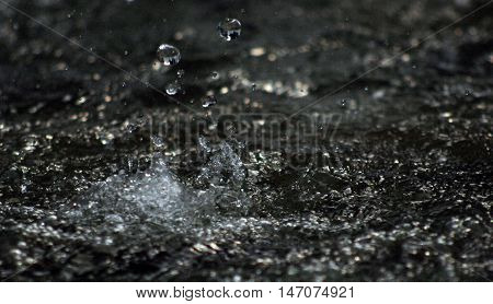 picture of a Water drops levitating in the air in dark. Splashing water fly in the air. Part of the drops is in focus part - out of the focus.