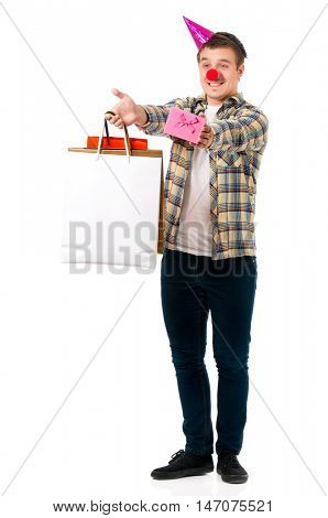 Handsome man clown isolated on white background. Teen boy with shopping bag making faces and wearing red nose.