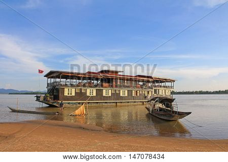 MEKONG, LAOS - MAY 2015 : Wooden boat in front of The Vat Phou Cruise 2 decks floating hotel, steel hulled teak barge, on Mekong River, Southern Laos on May 24, 2015.