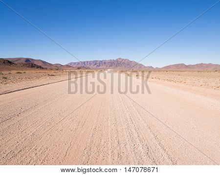 Empty gravel road in Namibia. Wide angle.