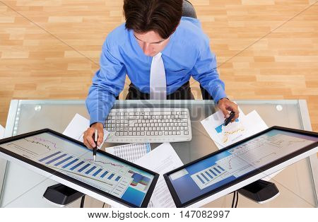Portrait of a Businessman Analyzing Charts and Graphs on Computer Monitors, Top View