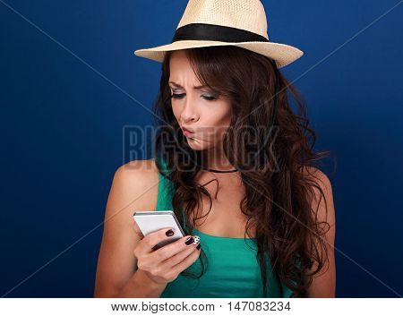 Grimacing Young Woman In Hat Looking On Mobile Phone With Question Sing On The Face On Blue Backgrou