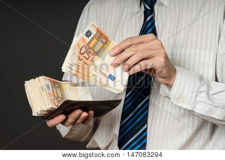 Businessman putting banknotes in his wallet. Stack of fifty euros money. Business man is holding cash. Person pays in euro bills isolated gray background.