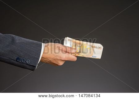 Businessman hand holding money euro bills. Banknotes isolated gray background. Hand holding out a stack of fifty euros