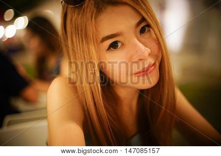 close up portrait of young asian woman smile and looking at camera with blurred background,selective focus,filtered warm tone process