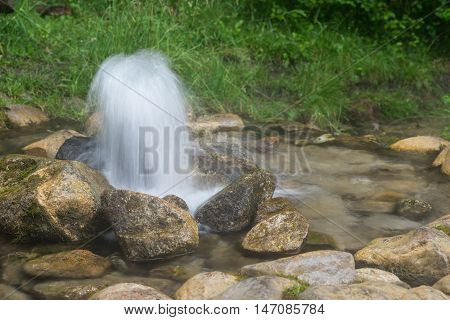 Artesian well. Eruption of spring natural environment. Stones and water. Clean drinking groundwater erupting out of the ground. Norra Spring Area Oostriku River Endla Nature Reserv Estonia Europe
