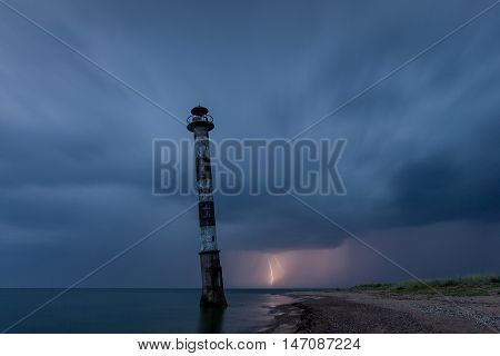Skew lighthouse in the Baltic Sea. Stormy night and lightning. Kiipsaar Harilaid Saaremaa Estonia Europe.
