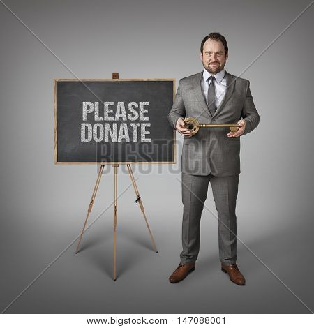 Please donate text on  blackboard with businessman and key