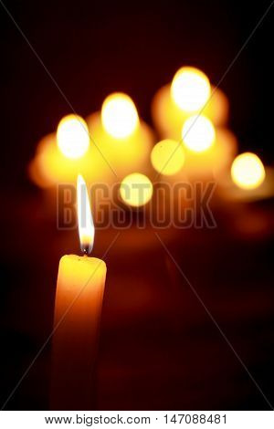 Candle in Focus with Blurred Candles in the Background