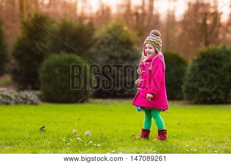 Happy little girl in pink warm coat and colorful knitted hat playing in beautiful autumn park on warm sunny fall day. Kids play with golden maple leaves.