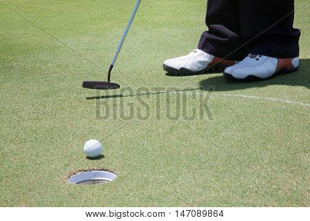 close up of golf ball rolling into a hole