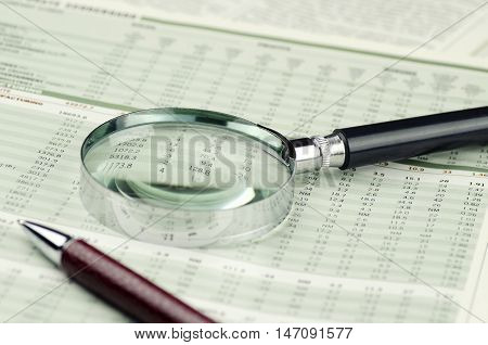 Loupe and Pen on Financial Documents - Close Up