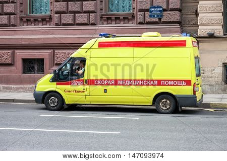 ST. PETERSBURG RUSSIA - JULY 31 2016: Emergency ambulance car with blue flashing light on the roof parked up on the city street. Text in russian: