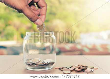 Close up of glass bottle with hand stacking silver coins on wooden table Save money concept Save money for prepare vintage style