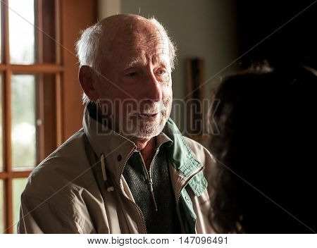 closeup of ninety years gentleman smiling and speaking to a lady - serial pictures