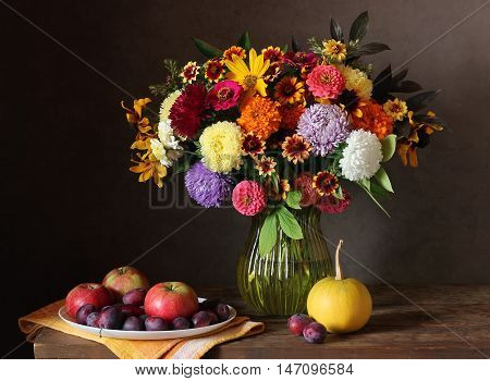 Still life with autumn bouquet of garden flowers in a vase plums apples and pumpkin.