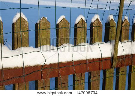 A wooden fence covered with white snow