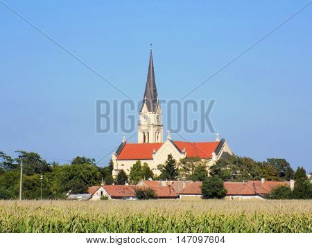Old catholic christian religion church behind corn field