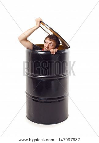 man looks out of a black barrel. the guy hid in a barrel. the young man lifted the lid and peeking out of the black barrel. isolated on white background