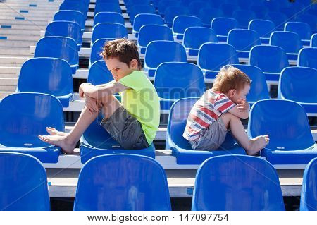 children quarreled. two disgruntled boys sitting facing away from each other. the concept of children's friendship