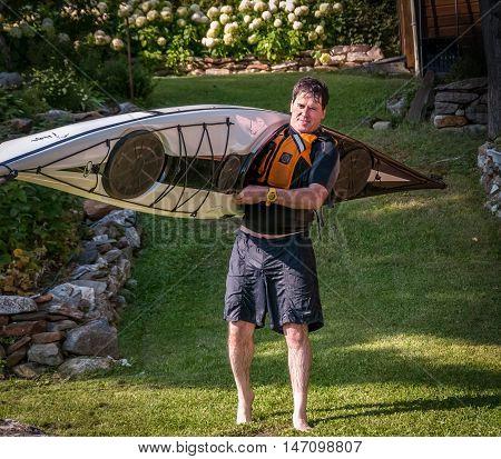 man transporting a kayak toward a lake