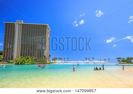 Waikiki, Oahu, HI - August 18, 2016: children play, swim, surf paddling in the lagoon at Hilton Hawaiian Village. The beach is one of more popular of Waikiki because offers a swimming area protected.