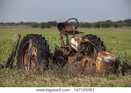 Abandoned and rusty tractor wastes away in field.
