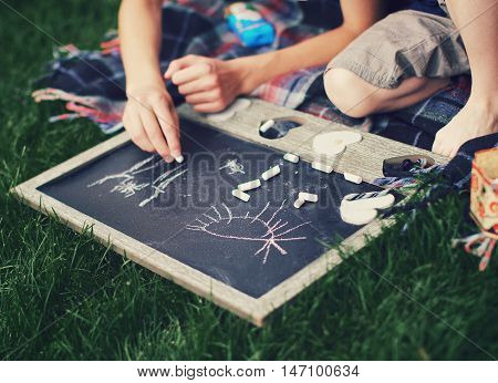 Children's hands are drawn on a board for drawing by chalk which lies on a grass