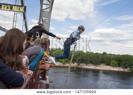 Kiev Ukraine - June 12 2016: Girl tries himself in the extreme sport jumping into gear with a bridge over the river