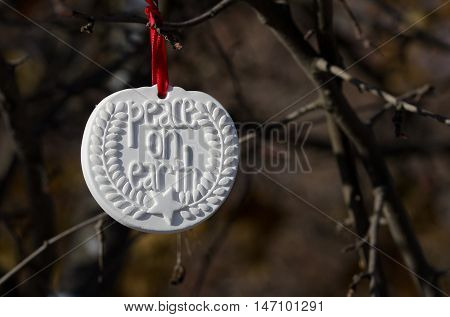 White Peace on Earth Christmas Ornament Hanging in the Winter Woods