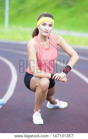 Young Caucasian Brunette Female in Athletic Sportgear Having Legs Stretching Excercises Outdoors. Vertical Image Orientation