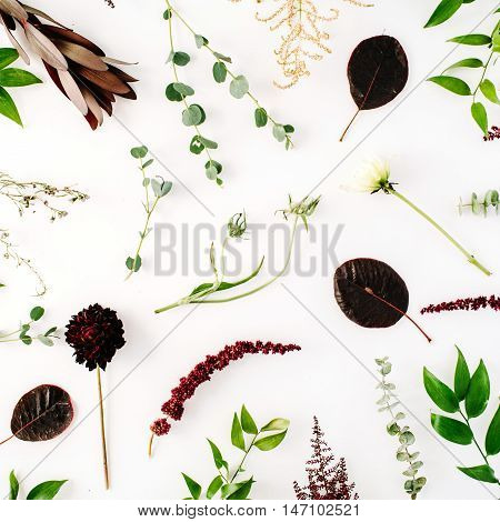 creative decorated and arranged flat lay pattern concept with green and purple branches on white background. top view
