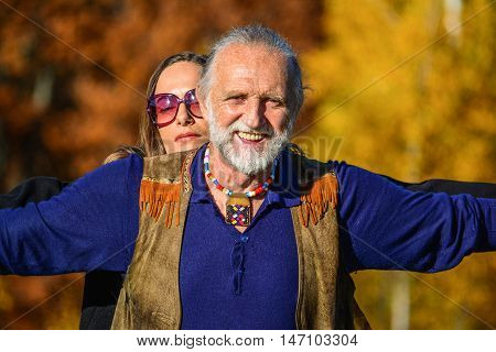 Portrait of good looking elderly man and woman enjoying life in a bright sunny autumn day