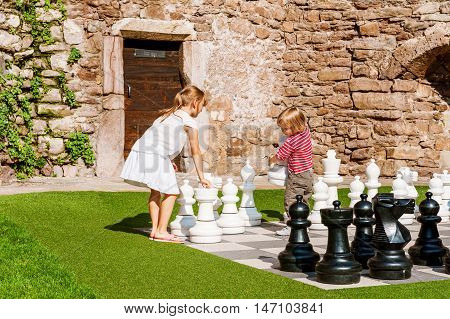 Two little kids playing giant chess outdoors