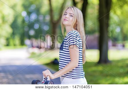 Teens Lifestyle Concepts and Ideas. Happy Smiling Caucasian Teenage Girl Posing With Long Skateboard Outdoors. Horizontal Image