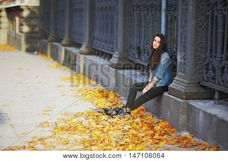 Young Pretty Woman Sitting Pensively On A Stone Slab A Beautiful Iron Fence With His Hands In The Po