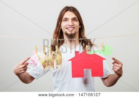 Concept of real estate and deal. Seller man with house model and banknotes. Selling and buying proposition.