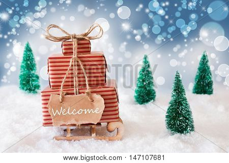Sleigh Or Sled With Christmas Gifts Or Presents. Snowy Scenery With Snow And Trees. Blue Sparkling Background With Bokeh Effect. Label With English Text Welcome
