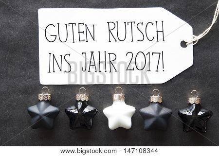 Label With German Text Guten Rutsch Ins Jahr 2017 Means Happy New Year 2017. Black And White Christmas Tree Balls On Black Paper Background. Christmas Decoration Or Texture. Flat Lay View
