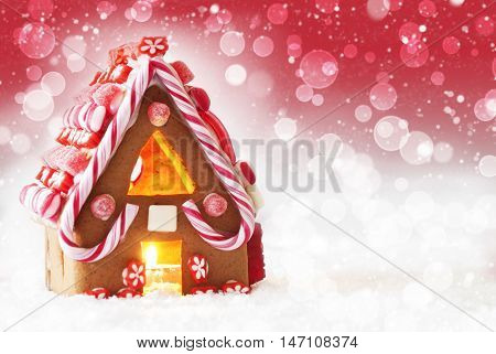 Gingerbread House In Snow As Christmas Decoration. Candlelight For Romantic Atmosphere. Red Background With Bokeh Effect And Snowflakes. Copy Space For Advertisement
